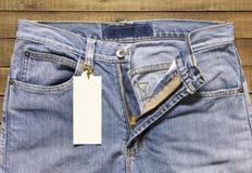Etiqueta e calças de brim da etiqueta no fundo de madeira fotografia de stock