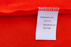 Etiqueta el 100 por ciento de algodón La inscripción en otros idiomas: Ruso, polaco, inglés, alemán Fotografía de archivo libre de regalías