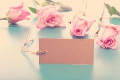 Etiqueta en blanco de la nota con las rosas rosadas Fotografía de archivo