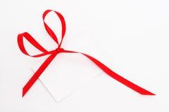 Etiqueta en blanco del regalo atada con la cinta roja Foto de archivo libre de regalías