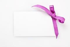 Etiqueta en blanco del regalo atada con un arco de la cinta de satén. Fotos de archivo
