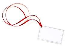Etiqueta en blanco del regalo con la cinta que se encrespa roja Fotos de archivo