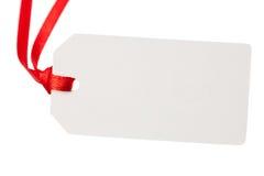 Etiqueta en blanco del regalo con la cinta roja imágenes de archivo libres de regalías