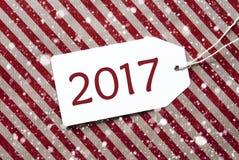 Etiqueta en el papel de embalaje y los copos de nieve rojos, texto 2017 Imágenes de archivo libres de regalías