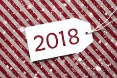 Etiqueta en el papel de embalaje y los copos de nieve rojos, texto 2018 Fotografía de archivo libre de regalías