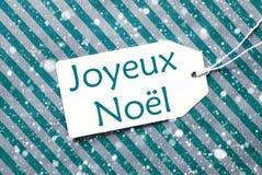 Etiqueta en el papel de la turquesa, copos de nieve, Joyeux Noel Means Merry Christmas Imágenes de archivo libres de regalías