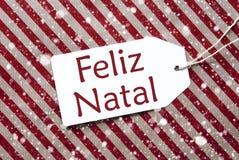 Etiqueta en el papel rojo, Feliz Natal Means Merry Christmas, copos de nieve Fotografía de archivo