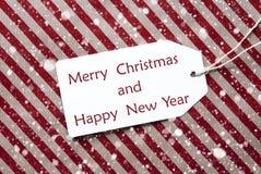 Etiqueta en el papel rojo, los copos de nieve, la Feliz Navidad y el Año Nuevo Imagen de archivo libre de regalías