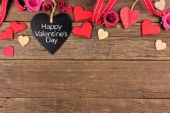 Etiqueta en forma de corazón feliz de la pizarra del día de tarjetas del día de San Valentín con la frontera contra la madera rús imagen de archivo libre de regalías