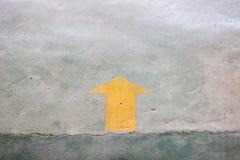 Etiqueta engomada amarilla de la flecha en el piso con el espacio de la copia Imagen de archivo libre de regalías