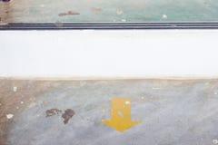 Etiqueta engomada amarilla de la flecha en el piso con el espacio de la copia Fotos de archivo