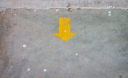 Etiqueta engomada amarilla de la flecha en el piso con el espacio de la copia Foto de archivo