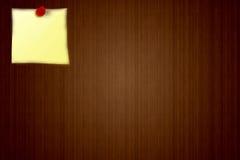 Etiqueta engomada amarilla en un fondo del tablero de madera del aviso Fotografía de archivo libre de regalías