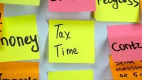 Etiqueta engomada con el tiempo del impuesto de las palabras en un whiteboard almacen de video