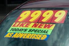 Etiqueta engomada del precio en la porción del coche usado Foto de archivo