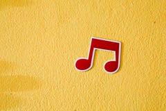 Etiqueta engomada plástica de la nota de la música en la pared del cemento Imagen de archivo libre de regalías