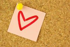 Etiqueta engomada rosada con el corazón del drenaje en el corkboard Imágenes de archivo libres de regalías