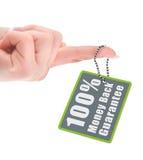 Etiqueta femenina de la garantía de la tenencia de la mano sobre blanco Imágenes de archivo libres de regalías