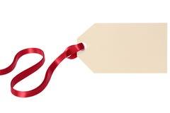 Etiqueta lisa do presente com a fita vermelha isolada no fundo branco Foto de Stock Royalty Free