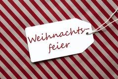 A etiqueta no papel de envolvimento vermelho, Weihnachtsfeier significa a festa de Natal fotos de stock royalty free