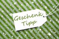A etiqueta, papel de envolvimento verde, Geschenk Tipp significa a ponta do presente, flocos de neve fotografia de stock