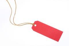 Etiqueta roja del regalo con la cuerda de oro Fotos de archivo