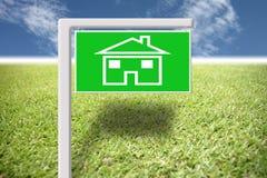 Etiqueta verde con la imagen casera en hierba y el cielo azul. Imagen de archivo