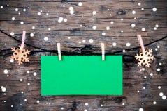 Etiqueta verde vacía con nieve en fondo de madera Foto de archivo libre de regalías