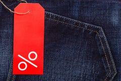 Etiqueta vermelha com sinal de por cento na sarja de Nimes Imagens de Stock Royalty Free