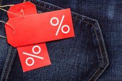 Etiqueta vermelha com sinal de por cento na sarja de Nimes Imagem de Stock Royalty Free
