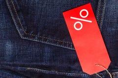 Etiqueta vermelha com sinal de por cento na sarja de Nimes Imagem de Stock
