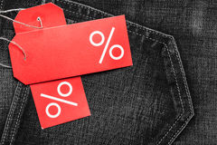 Etiqueta vermelha com sinal de por cento na sarja de Nimes Fotografia de Stock