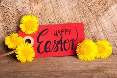 Etiqueta vermelha, dente-de-leão, Páscoa feliz da caligrafia inglesa fotos de stock royalty free