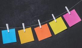 Etiquetas coloridas brilhantes em uma corda em um fundo escuro Imagem de Stock