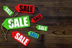 Etiquetas coloridas da venda no copyspace de madeira escuro da opinião superior do fundo Fotografia de Stock Royalty Free