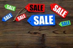 Etiquetas coloridas da venda no copyspace de madeira escuro da opinião superior do fundo Imagens de Stock Royalty Free