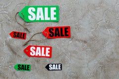 Etiquetas coloridas da venda no copyspace de pedra claro da opinião superior do fundo Imagens de Stock