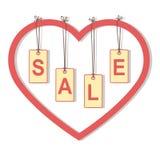"""Etiquetas com as letras """"SALE"""" que penduram em cordas dentro do coração Imagens de Stock"""