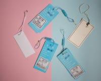 etiquetas da roupa no rosa e no fundo azul foto de stock