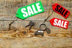 Etiquetas da venda e chaves coloridas do carro no copyspace de madeira da opinião superior do fundo Fotografia de Stock