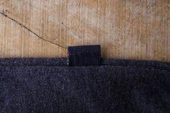 Etiquetas de la ropa en fondo de madera foto de archivo