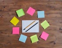 Etiquetas engomadas coloreadas alrededor del cuaderno en la tabla Imagen de archivo