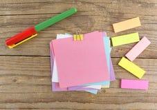 Etiquetas engomadas coloreadas alrededor del cuaderno en la tabla de madera vieja Imágenes de archivo libres de regalías
