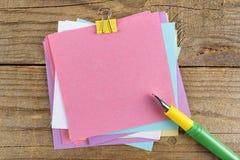 Etiquetas engomadas coloreadas alrededor del cuaderno en la tabla de madera vieja Fotografía de archivo
