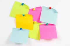 Etiquetas engomadas coloridas en el tablero de mensajes blanco Fotos de archivo