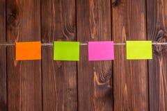 etiquetas engomadas coloridas que cuelgan en cuerda para tender la ropa contra backgrou de madera Fotografía de archivo libre de regalías
