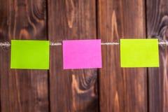 etiquetas engomadas coloridas que cuelgan en cuerda para tender la ropa contra backgrou de madera Fotografía de archivo