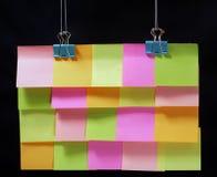 Etiquetas engomadas coloridas que cuelgan en los clips, primer, fondo oscuro imagenes de archivo