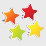 Etiquetas engomadas de la estrella fijadas con las tijeras Imagenes de archivo