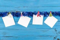 Etiquetas engomadas de papel y ornamentos y juguetes del Año Nuevo en fondo de madera azul Foto de archivo libre de regalías